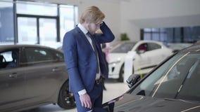 Bärtiger Geschäftsmann, der oben Auto im Verkaufsstelleabschluß wählt Hohe Mannschreibschrift durch Haar nahe Automobil in der Au stock video