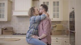 Bärtiger Mann steht nahe der hübschen Frau, die auf Tabelle in der großen halb leeren Küche sitzt Frau umarmt ihren Ehemann, sie  stock footage