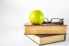 Bücher und Apfel auf weißem Hintergrund lizenzfreies stockfoto
