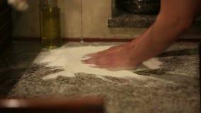 Bäcker übergibt knetenden Teig im Mehl auf Tabelle stock footage