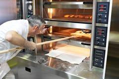 Bäcker backt Brot im Ofen stockbild