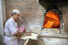Bäcker breitete Teig auf Schaufel aus, um sie im Ofen zu senden Stockfotografie