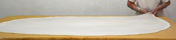 Bäcker dehnt den Teig aus Stockfoto