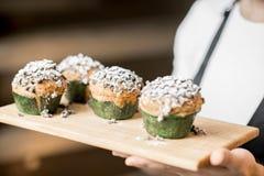 Bäcker, der maffins in der Bäckerei hält Lizenzfreies Stockfoto