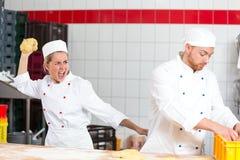 Bäcker, der mit werfendem Teig des Kollegen an ihm frustriert ist lizenzfreie stockfotos