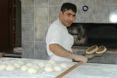 Bäcker gibt Kuchen zum Ofen Lizenzfreies Stockfoto