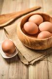 Bäcker mit Bestandteilen für Gebäcknachtische Küchengeräte und Backenbestandteile: Ei und Mehl auf hölzernem Hintergrund Stockfotografie