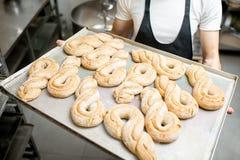 Bäcker mit dem Behälter voll vom süßen Gebäck Stockfotos
