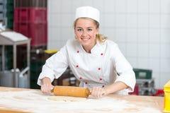 Bäcker mit der Teigrolle, die in einer Bäckerei arbeitet stockfotos