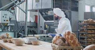 Bäcker mit einem Barttanzen lustig in einer Backwarenindustrieküche bei der Zubereitung des Teigs für backendes Brot, Nahrungsmit stock video
