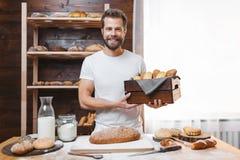 Bäcker mit einer Vielzahl des köstlichen frisch gebackenen Brotes und des Gebäcks Stockbilder