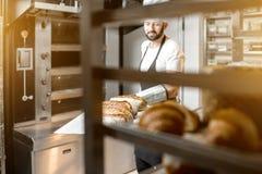 Bäcker mit gebackenen Broten an der Bäckerei Lizenzfreies Stockbild