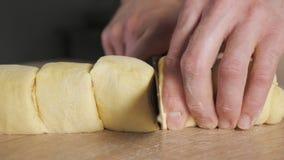 Bäckerchef schneidet Rolle mit Zimt, Zucker und Butter auf Teilen, um Zimtgebäck zu backen stock video
