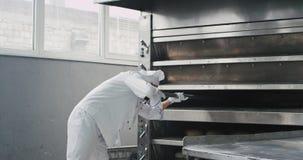 Bäckerchef und seine Unterstützung zwei in der Bäckereifabrik entfernen das gekochte Brot von der industrieller Ofenmaschine und  stock video footage