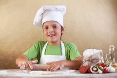 Bäckerchefjunge, der den Teig ausdehnt Stockbilder