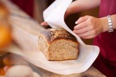 Bäckerei-Arbeitskraft, die Brot am Zähler einwickelt Stockbilder