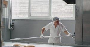 Bäckereiarbeitskraft ausgerüstet in einer weißen Uniform, das Brot von der industriellen Ofenmaschine unter Verwendung einer spez stock video