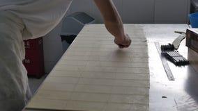 Bäckereiarbeitskraft-Ausschnittteig bedeckt für Hörnchen in der industriellen Küche stock footage