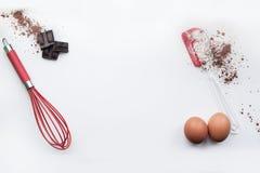 Bäckereibestandteile - Mehl, Eier, Kakao, Schokolade auf weißer Tabelle Süßes Gebäckbackenkonzept Flache Lage, Kopienraum, Draufs stockbilder