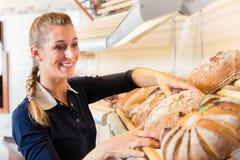 Bäckereifrau, die Brot in Shopregal einsetzt stockfotografie