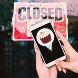 Bäckereishop mit Kartenzeiger auf Smartphone, geschlossener Fall auf dem d Stockfotografie
