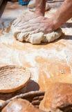 Bäckerhände, die Teig kneten Stockfoto
