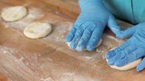 Bäckerhand in den Handschuhen, die Teig für Gebäck auf Holztisch im Bäckereishop rollen lizenzfreie stockbilder