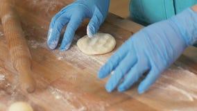 Bäckerhand, die Bälle vom Teig für Pastetchen auf Holztisch im Bäckereishop macht stockfotografie