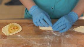 Bäckerhand, die Pastetchen bildet, nachdem auf Holztisch im Bäckereishopabschluß auffüllen lizenzfreie stockfotografie