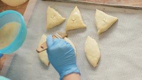 Bäckerhand fügt Eimischung mit Bürste auf Pastetchen zu, bevor sie auf Tabelle backt stockbilder