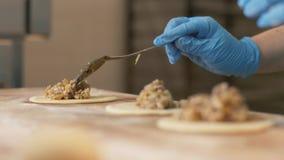 Bäckerhandfüllender Teig und Formungspastetchen auf Tabelle in der Bäckereishopnahaufnahme stockbild