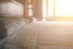 Bädda ned i sovrum med soluppgångeffekt, hyr rum det rena vita sängkläderarket och kuddar i skönhet inre Fotografering för Bildbyråer