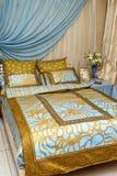 Bädda ned i sovrummet med de blåa guld- linnarna Arkivbild