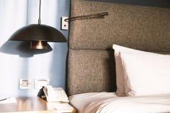 Bädda ned med en kudde, en tabell, en lampa och en telefon Arkivfoto