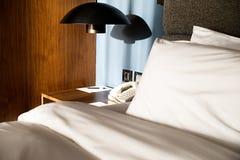 Bädda ned med en kudde, en tabell, en lampa och en telefon Royaltyfri Fotografi