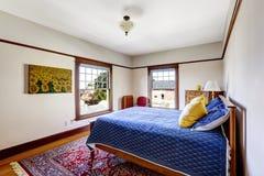Bädda ned med ljus blå sängkläder och gulna kuddar Arkivfoton