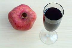 Bägare av wine och en pomegranate på bordlägga royaltyfria foton