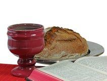 Bägare, bröd och bibel på vit bakgrund Arkivbilder