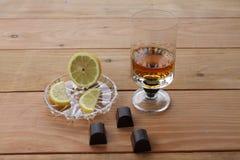 Bägaren för konjak för konjakcitronskivor av kväv whiskychokladcitronen på en träbakgrund med Arkivfoton