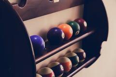 Bälle für Poolbillard im Regal, Billardkugeln für das amerikanische Billard gefärbt auf einem hölzernen Hintergrund Lizenzfreie Stockfotos