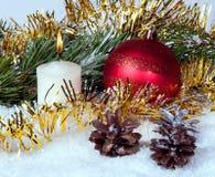 Bälle, Kerze und Tannenzapfen des neuen Jahres unter Lametta und Zweigen Lizenzfreie Stockfotos