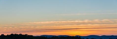 Bänder von gelben und orange Cirrus-Wolken Stockfotos