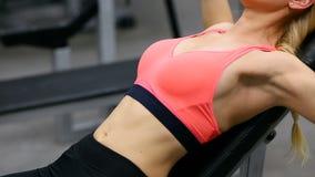 Bänk för ung kvinna som trycker på med hantlar i idrottshallen, den funktionsdugliga tricepens och bröstkorgen stock video