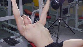 Bänk för ung man som trycker på vikter på en idrottshall lager videofilmer
