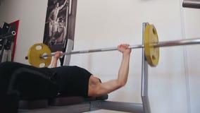 Bänk för ung man som trycker på vikter på en idrottshall arkivfilmer