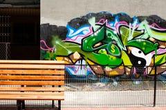 Bänk framme av en grafittivägg Royaltyfri Foto