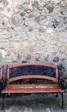 bänk framme av en stenvägg Royaltyfri Fotografi