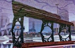 Bänk i en pölreflexion uppochnervända Yekaterinburg i city royaltyfri bild