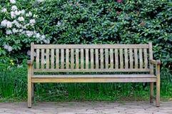 Bänk i en trädgård! Arkivfoto