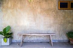 Bänk med den dekorativa växten på betongväggbakgrund Arkivfoto